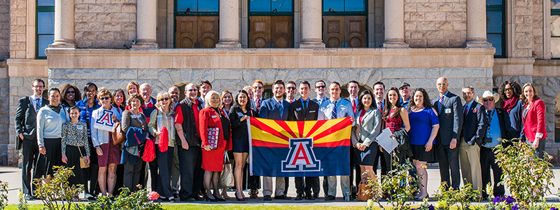 Students/Alumni holding a University of Arizona flag