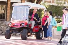 President Robbins with students in golf cart